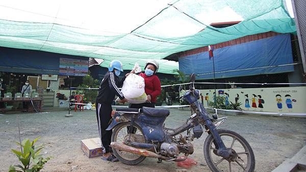 Une famille récupère un sac de riz