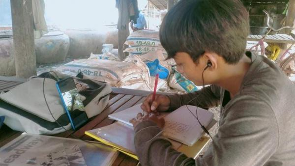 Un élève continue d'étudier chez lui en se connectant aux cours à distance via un smartphone prêté p