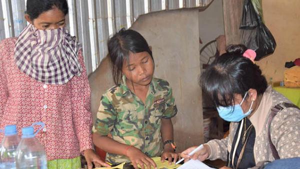 Une employée de PSE enregistre une mère et sa fille avant la distribution