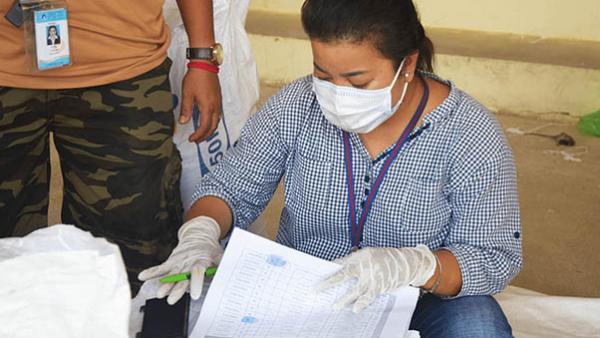 Une employée de PSE vérifie les listes pour la distribution de riz