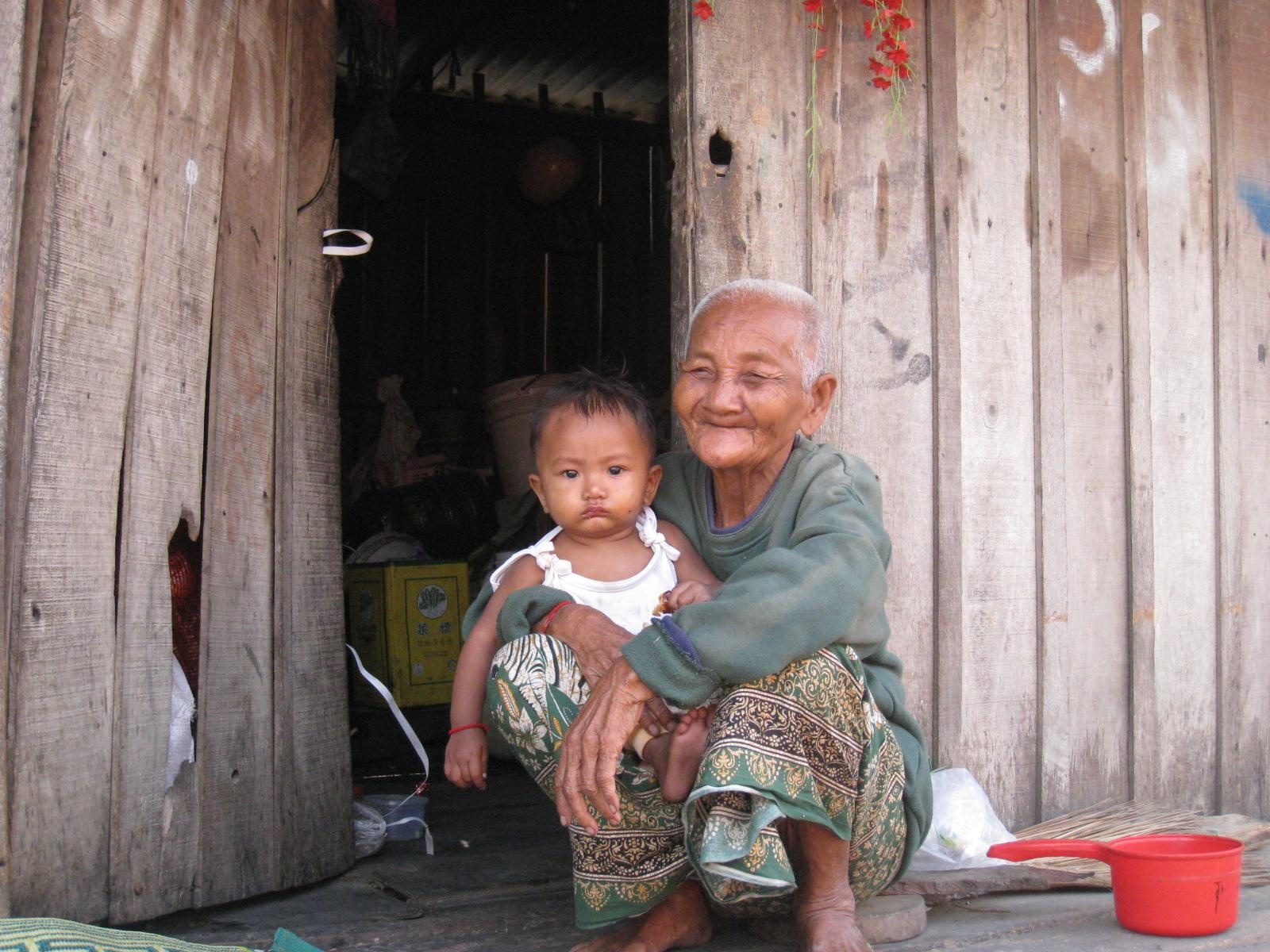 Une veille dame et son petit-enfant devant leur habitation dans une zone de grande pauvreté